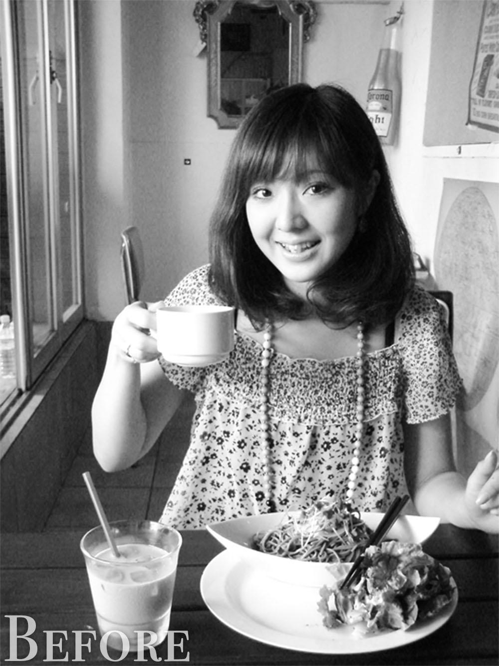 カフェで食事する女性のモノクロ写真